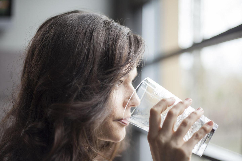 Trockener Mund: Frau trinkt Glas Wasser