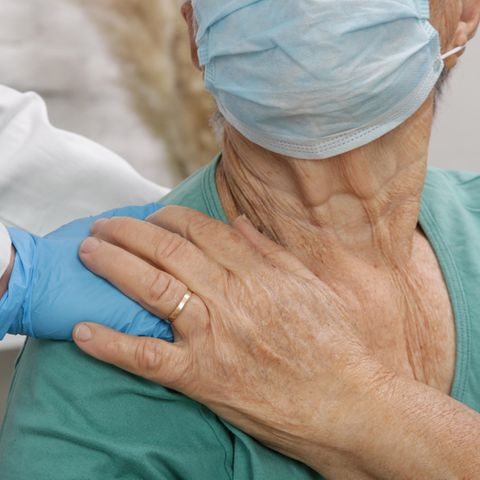 Corona aktuell: Älterer Frau liegt Hand auf Schulter