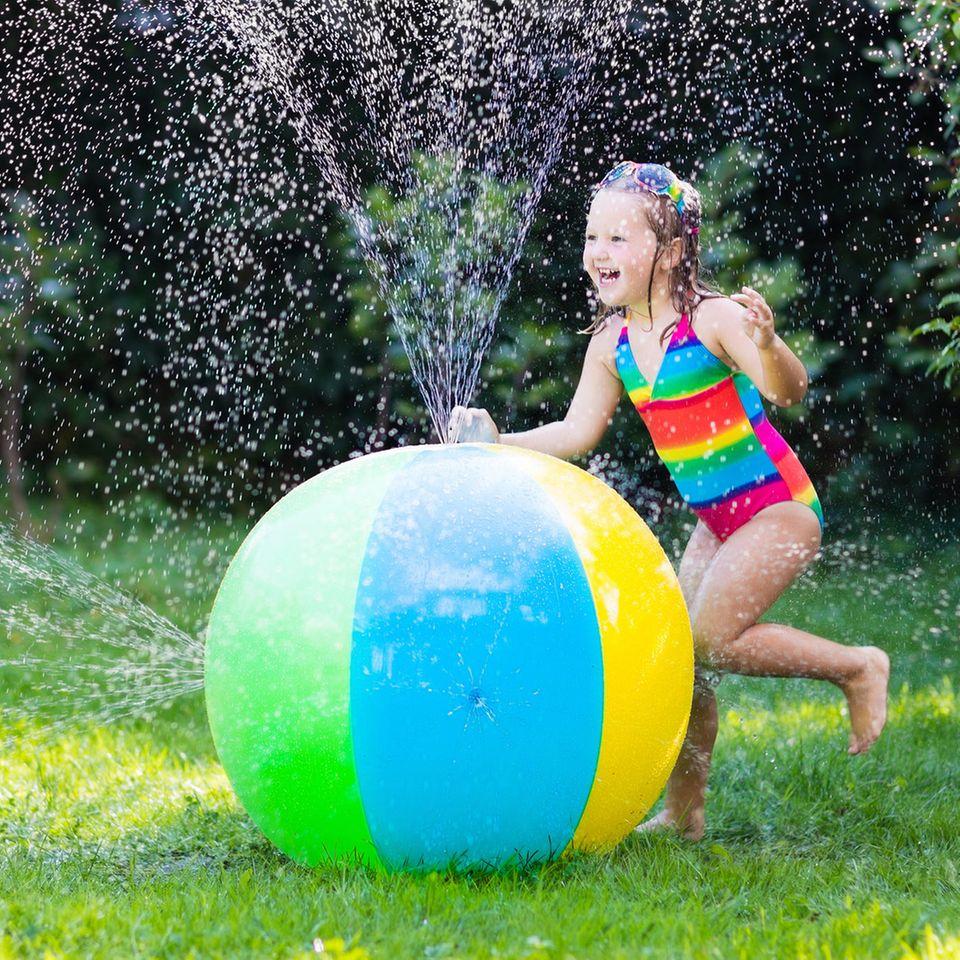 Wasserspielzeug: Mädchen in Badeanzug mit Wasserspielzeug im Garten, bunter Wasserball mit Düsen für Kinder