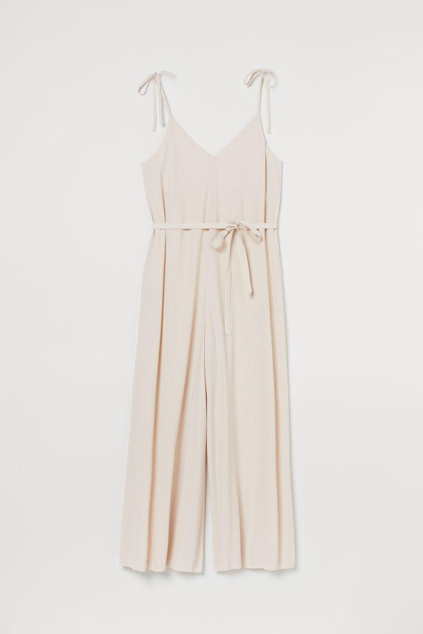 Es muss nicht immer ein Kleid sein, wenn es um luftige Sommerlooks geht. Dieser cremefarbene Jumpsuit mit extraweitem Bein und süßen Trägern zum Selberbinden aus einem Lyocellmix ist der perfekte Buddy an heißen Tagen. Von H&M, um 30 Euro.