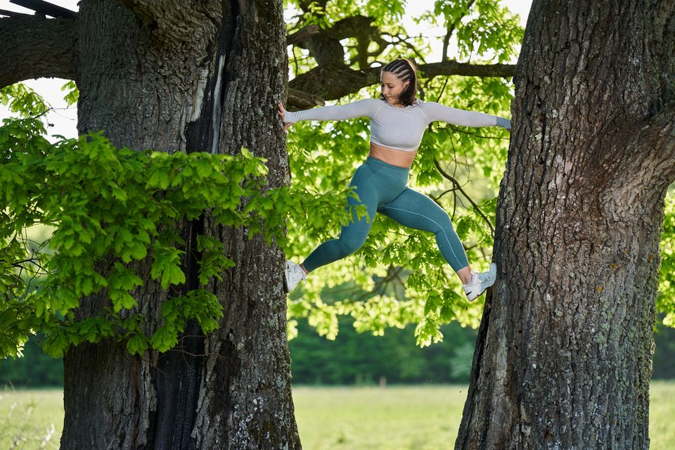 Natural Movement: Frau klettert Baum hoch