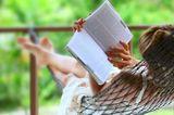 Horoskop: Eine Frau liegt in der Hängematte und liest