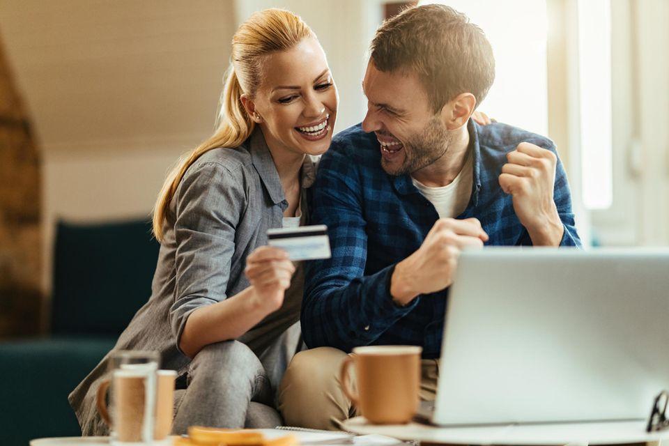 Glückliches Paar beim Online-Shopping, Frau mit Kreditkarte, Laptop, Kaffeetassen