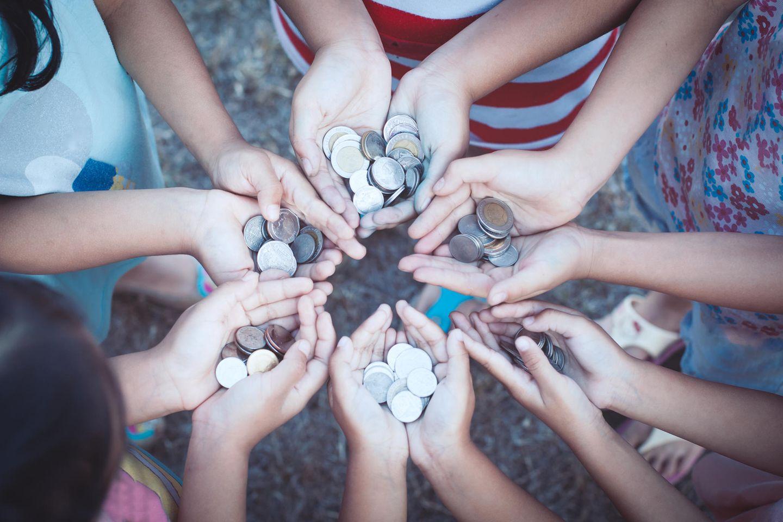 Umgang mit Geld: Kinder halten Münzen in den Händen