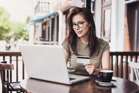 Junge Frau am Online-Shoppen, Kreditkarte in der Hand, Kaffee und Laptop auf dem Tisch