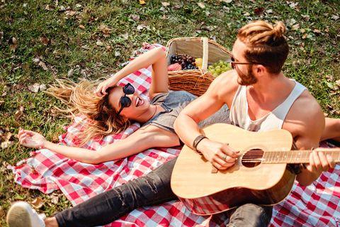 Beziehung: Ein Pärchen mit Gitarre beim Picknick im Park