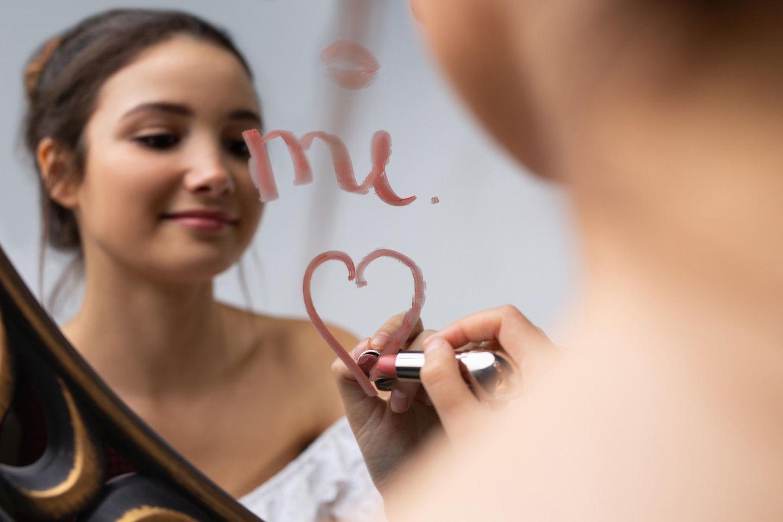 Selbstliebe: Frau malt Herz mit Lippenstift auf einen Spiegel