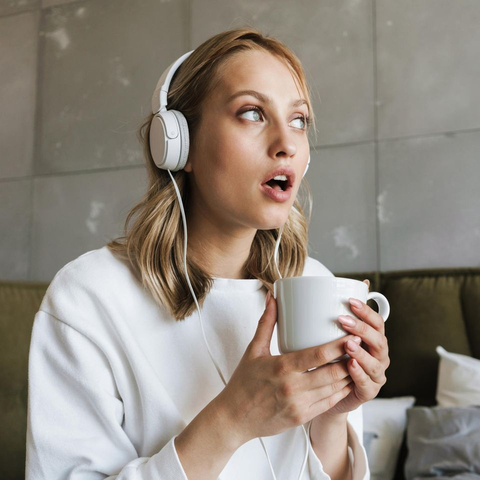 Akustische Illusion: Frau mit Kopfhörern lauscht konzentriert im Cafè