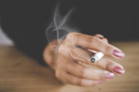 Rauchen aufhören: Frauenhand mit Zigarette