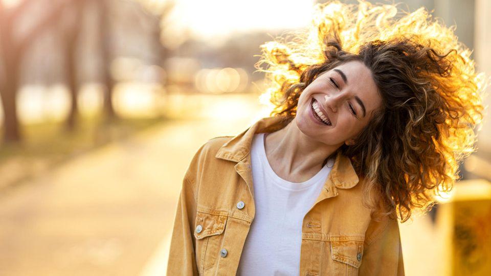 Horoskop: Eine fröhliche lockige Frau
