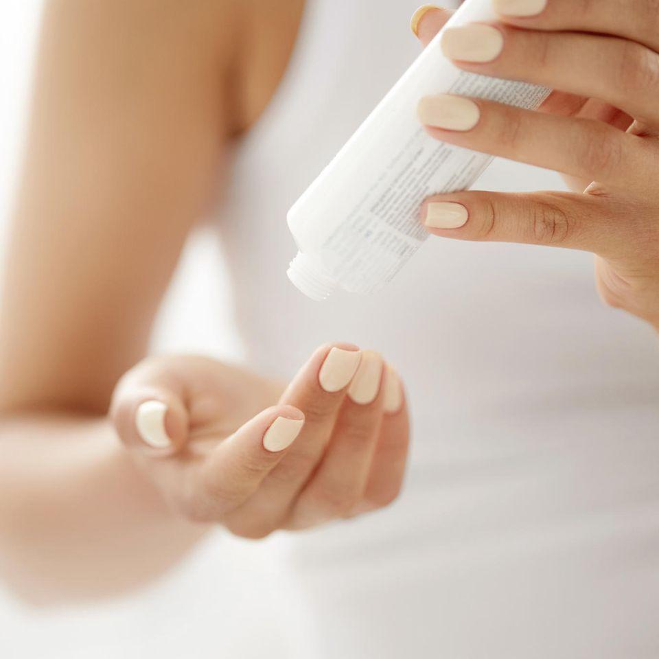 Handcreme Test: 7 Produkte im Vergleich, Eine Frau hat eine Cremetube in den Händen