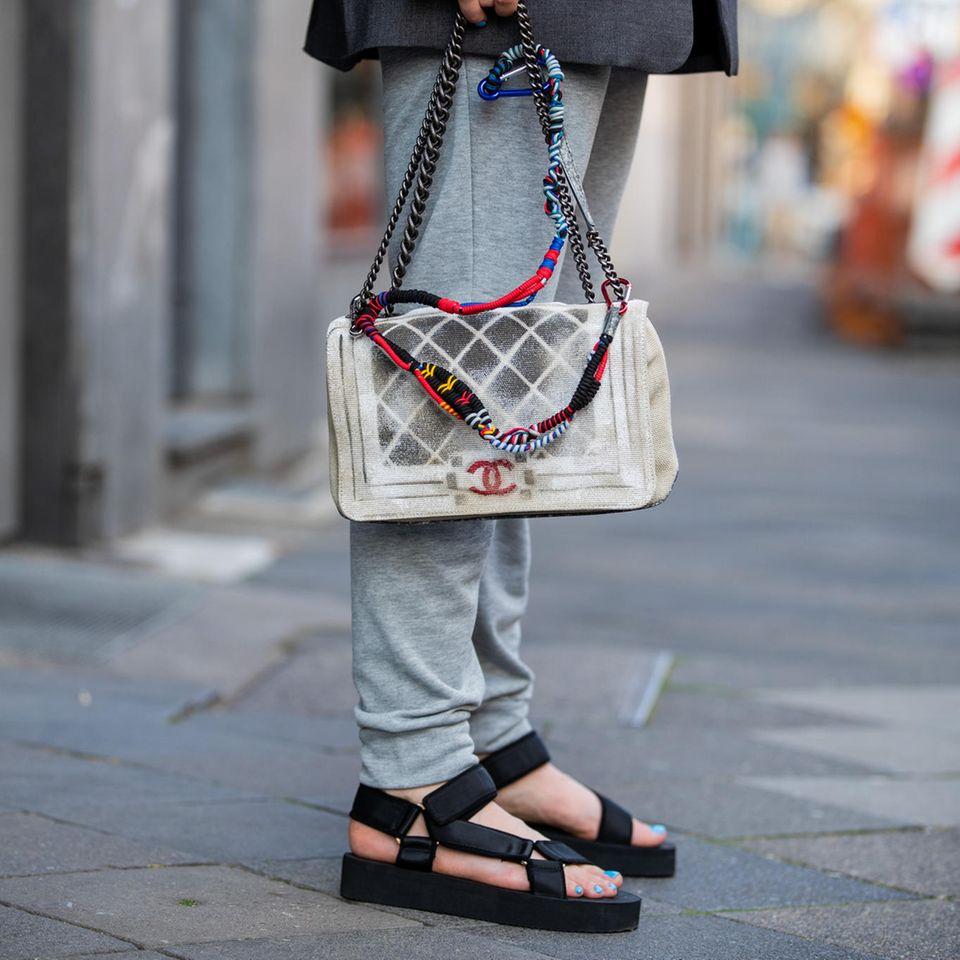 Trekkingsandalen: Frau mit Sandalen und Chanel-Tasche