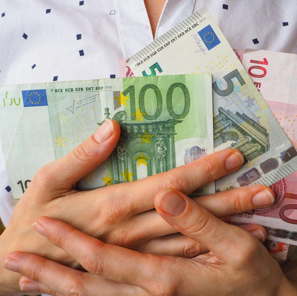 Passives Einkommen: Frau hält Geldscheine vor der Brust