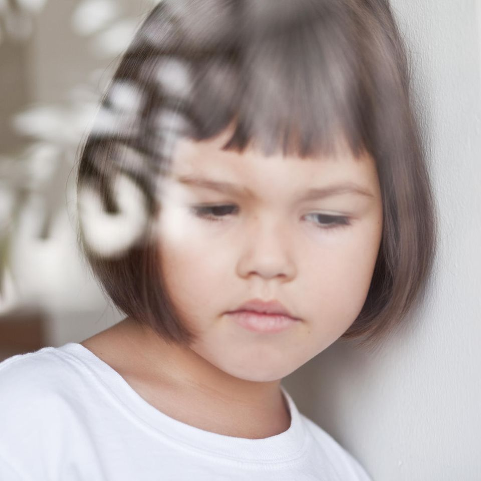 Arme Familien: Mädchen lehnt traurig an Wand