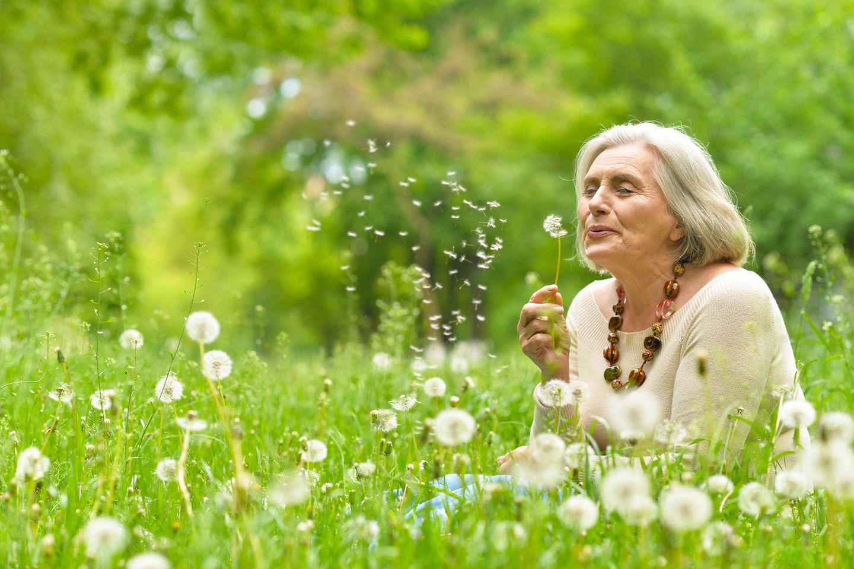 Horoskop: Eine ältere Frau mit Pusteblume