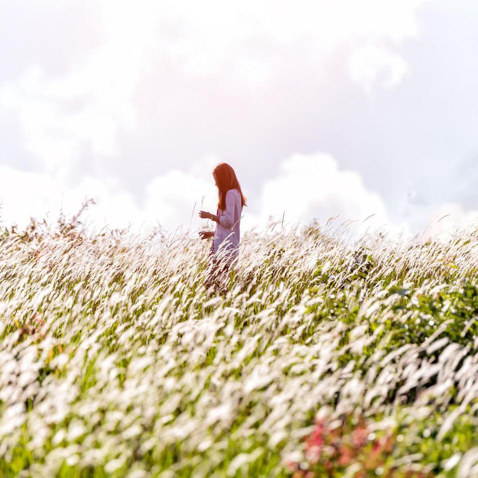 Psychologie: Eine Frau steht auf einer Blumenwiese und grübelt