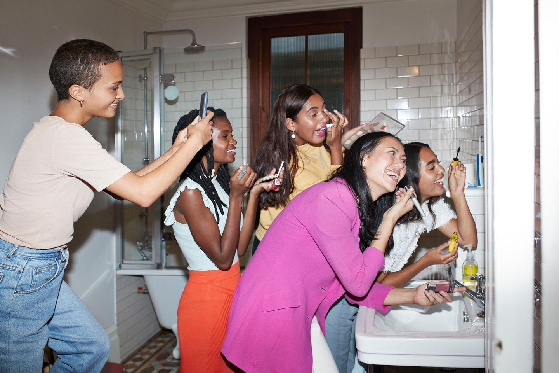 Beauty: Frauen schminken sich vor dem Spiegel
