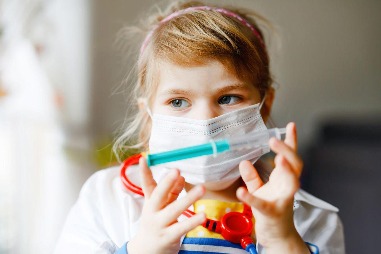 Corona-Risiko bei Kindern: Mädchen mit Mund-Nasen-Schutz und Spritze
