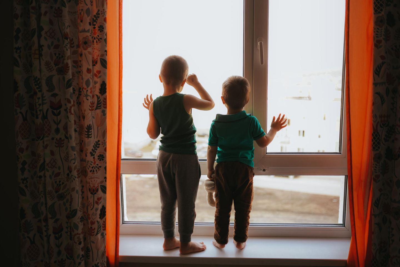 Armutsfalle Hartz4: 2 Kinder schauen durchs Fenster nach draußen
