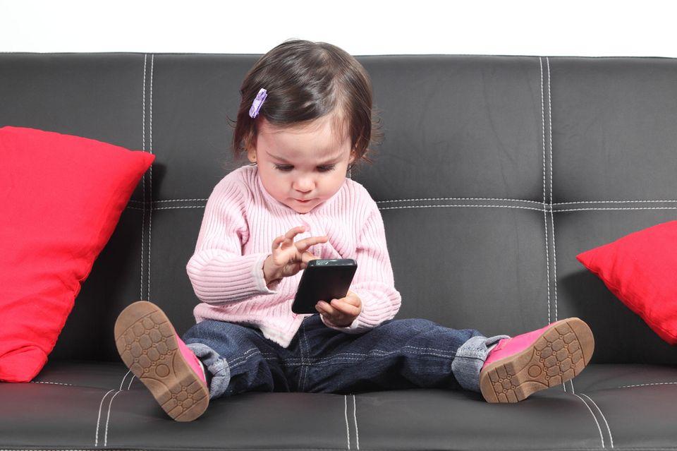 #meinkindtwittert: Kleinkind mit Handy auf einem schwarzen Sofa