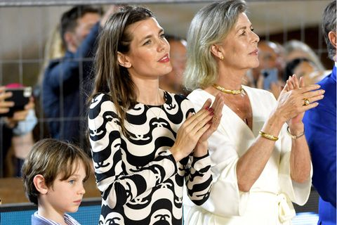 Der Look der Royals: Prinzessin Caroline, Charlotte Casiraghi und Sohn Raphael Casiraghi stehen nebeneinander und klatschen.