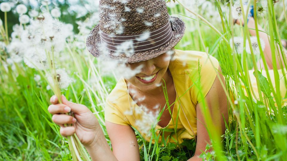 Horoskop: Eine Frau mit Hut und Pusteblume