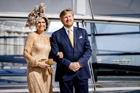 Bei ihrem Besuch in Berlin setzt Königin Máxima auf einen Look, der uns verdächtig bekannt vorkommt: Sie trägt ein beigefarbenes, halbtransparentes Kleid mit einem Blüten-Hut. Der besondere Hut lässt schon vermuten, wo Máxima das Outfit bereits getragen hat ...