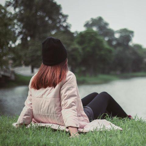 Beziehung: Eine junge Frau sitzt am See
