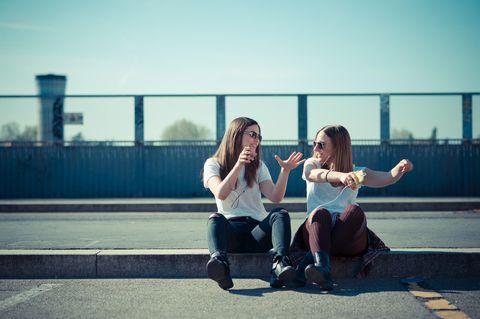 PSychologie: Zwei Freundinnen sitzen auf dem Bürgersteig und tanzen
