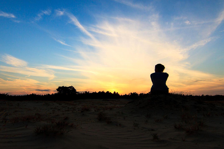 Horoskop: Eine Frau sitzt auf einem Hügel bei Sonnenuntergang