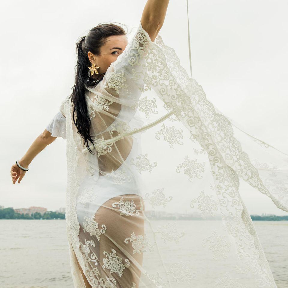 Durchsichtige Kleidung: Dunkelhaarige Frau in weißem Badeanzug mit durchsichtigem Kimono drübergezogen