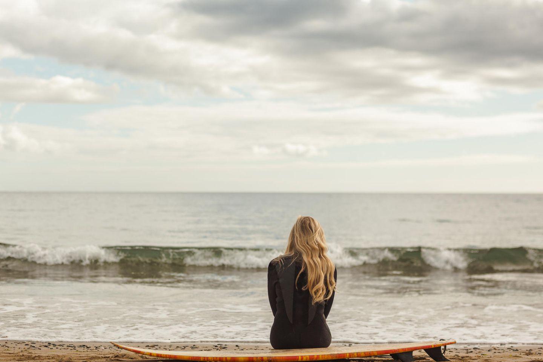 Psychologie: Eine Frau sitzt am Strand auf einem Surfbrett