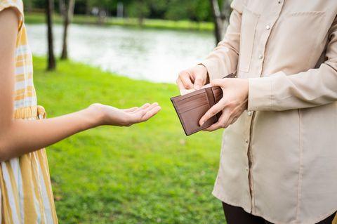 Taschengeld: Mädchen hält die Hand auf, während ihre Mutter ihr Taschengeld gibt
