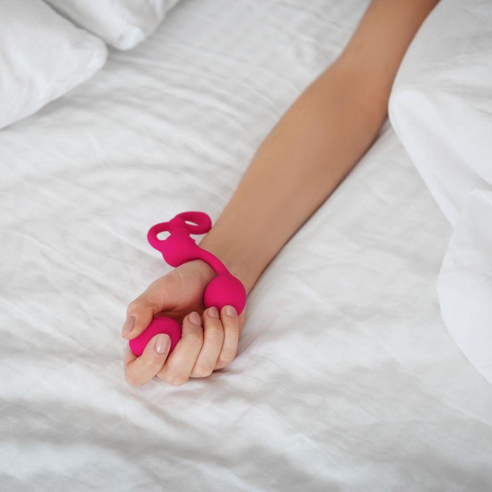 Liebeskugeln: So funktionieren sie, Frau hält pinke Liebeskugeln in der Hand