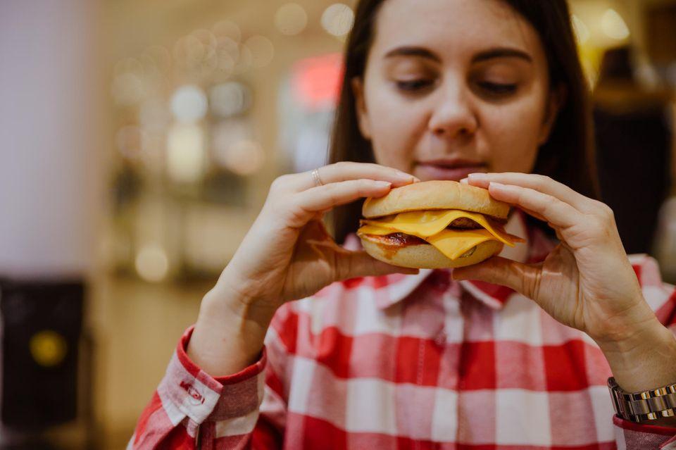 Leckerer Anreiz: Frau beißt in Burger