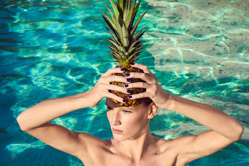Früchte für die Schönheit: Frau im Pool mit Ananas