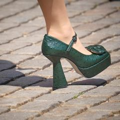 Die dunkelgrünen Plateau-Pumps mit Riemchen von Morobé stechenbesonders durch ihren besonders geformten Absatz ins Auge. Eine Applikation in Flechtoptik verziert den vorderen Teil des Schuhs. Auffällig, aber mit Sicherheit nicht jedermanns Geschmack.