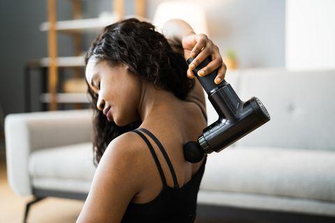 Massagepistole Test: Die besten 6 Modelle, Frau benutzt eine Massagepistole am Nacken
