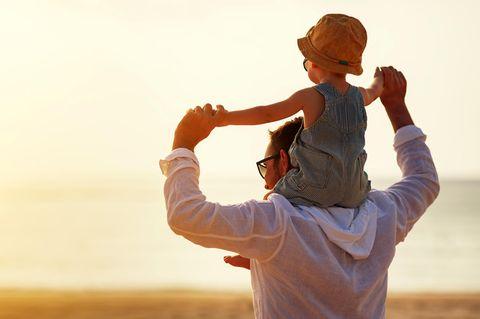 Rollentausch: Vater trägt Sohn auf Schultern