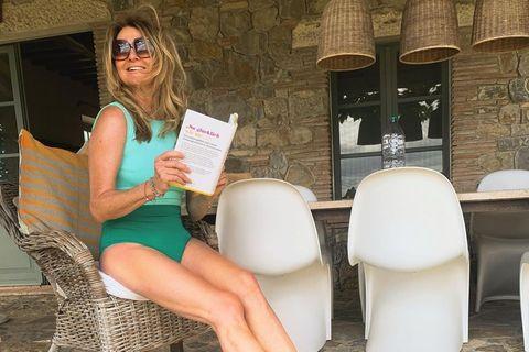 Frauke Ludowig sitzt im Badenazug mit einem Buch auf der Terrasse ihres Ferienhauses.