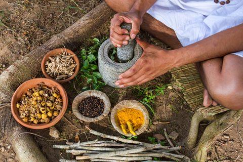 Ayurvedische Ernährung: Mann zerkleinert Lebensmittel mit Mörser