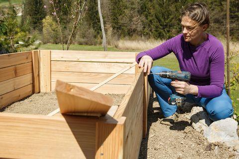 Hochbeet selber bauen: Einfach Anleitung fürs DIY-Projekt, Frau mit Bohrer
