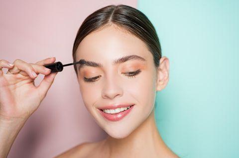 Eine Frau kämmt sich die Augenbrauen mit einem Bürstchen und lächelt dabei.