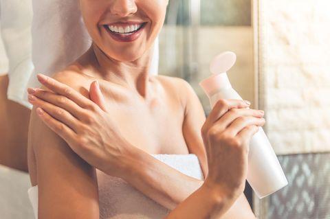 Eine Frau, die gerade aus der Dusche kommt, pflegt ihren Körper mit Bodylotion.