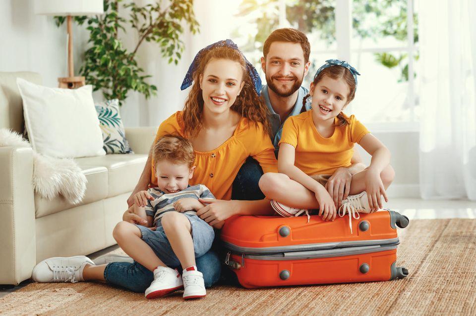 So machst du deine Wohnung urlaubsfit: Familie sitzt auf gepackten Koffern
