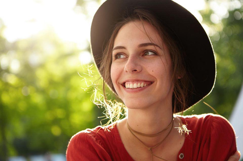Horoskop: fröhliche Frau mit Hut