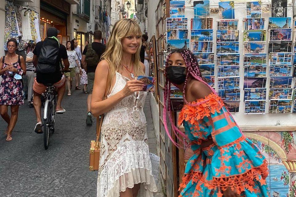 Beim Postkarten-Shopping gesellt sich plötzlich Heidi Klums Tochter Lou dazu und photobombt die Aufnahme ihrer Mutter. Dass Heidi so viel von ihrer Jüngsten auf ihrem Instagram-Profil zeigt, ist eine absolute Seltenheit. Optisch setzt das Mutter-Tochter-Duo auf Spitze:Heidi in Weiß mit Vokuhila-Schnitt, die elf-Jährige trägt ein Volant-Kleid in den Farben Orange und Türkis.