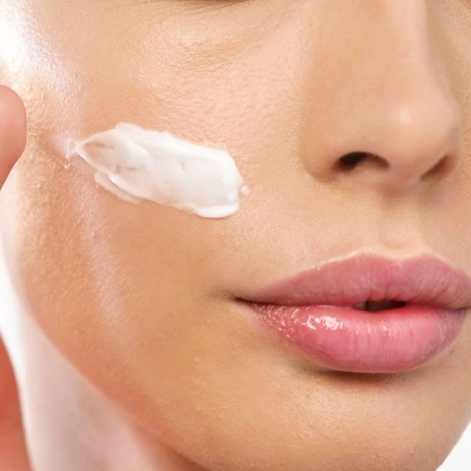 Hautpflege: Frau cremt sich das Gesicht ein