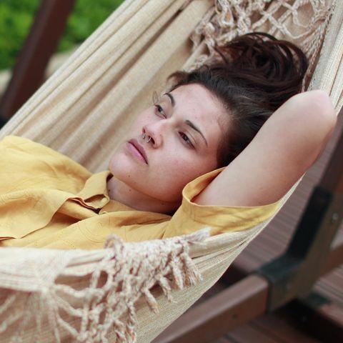 Psychologie: Eine Frau liegt in einer Hängematte und denkt nach