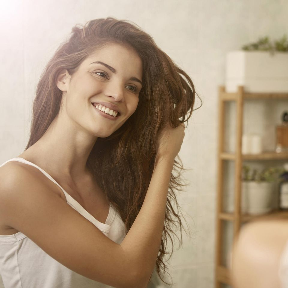 Eine Frau schaut sich im Spiegel an und fährt sich durch die Haare.